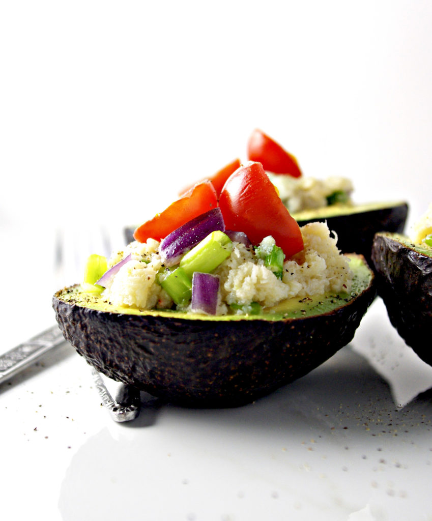 An avocado topped with seasoned crab meat, onions, and tomatoes | via spiritedandthensome.com