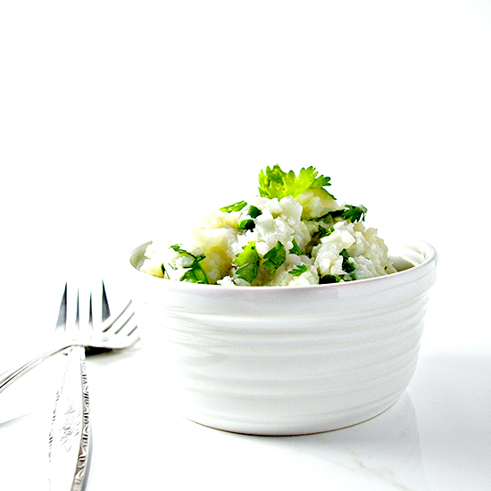 Seasoned Cauliflower Mashed Potatoes in white porcelain dish on a white marble slab with silverware.
