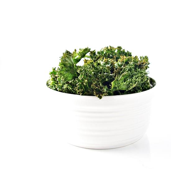 Crispy Kale Chips in a porcelain dish | via spiritedandthensome.com