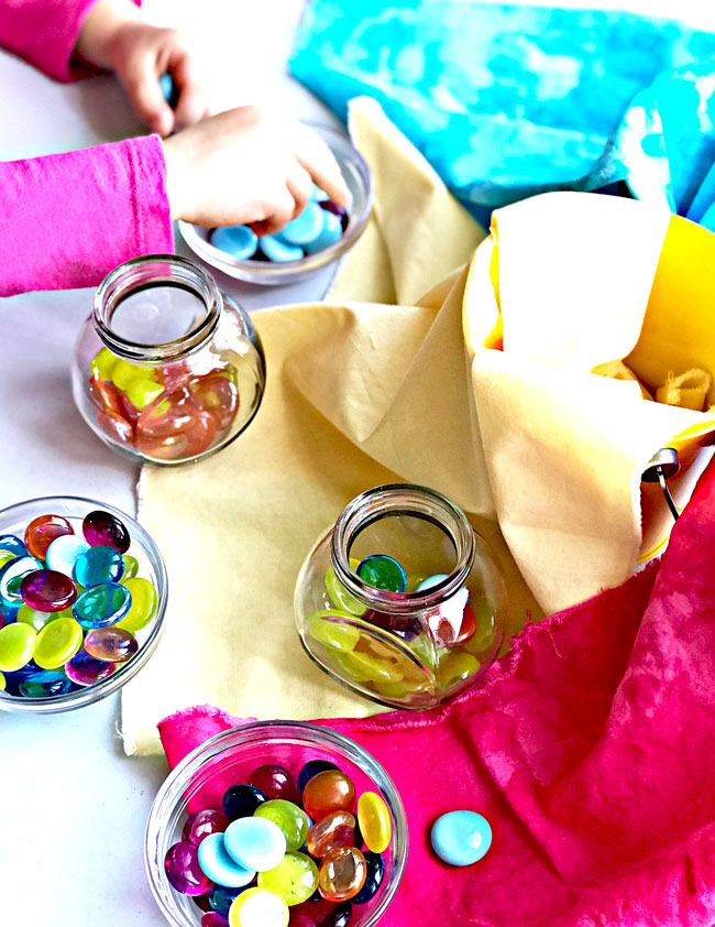 Glass beads, flat marbles, and gems are used in sensory play activities for children! | spiritedandthensome.com