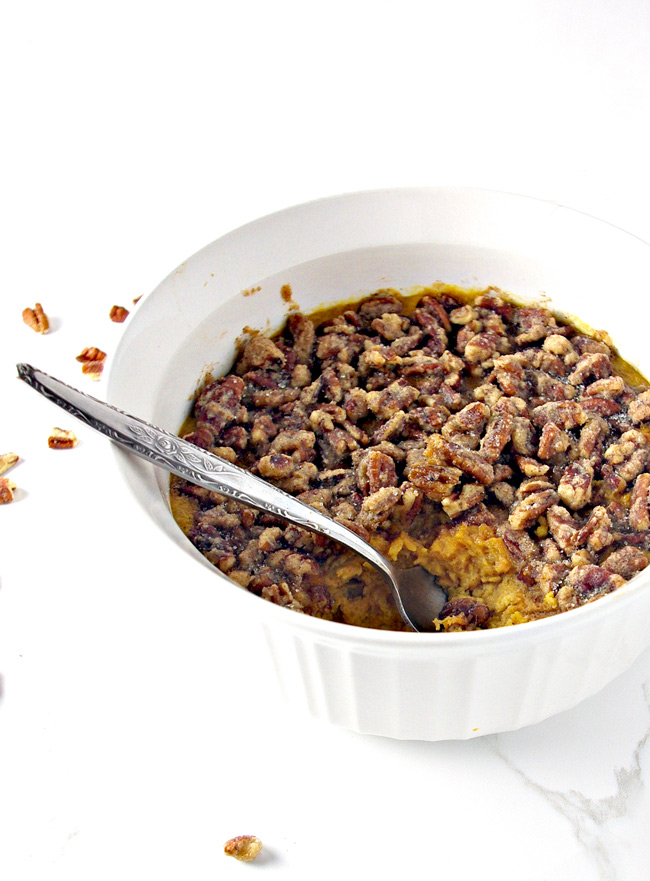 Paleo Sweet Potato Casserole is topped with chopped pecans that have been mixed in a maple cinnamon drizzle! | spiritedandthensome.com
