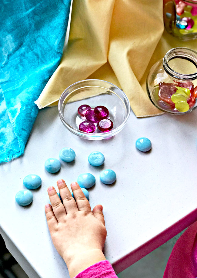 Flat marbles and gems are perfect low-cost sensory play activities for children! | spiritedandthensome.com