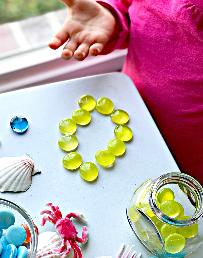 Building a sun using flat marbles or gems is a great sensory activity for children! | spiritedandthensome.com