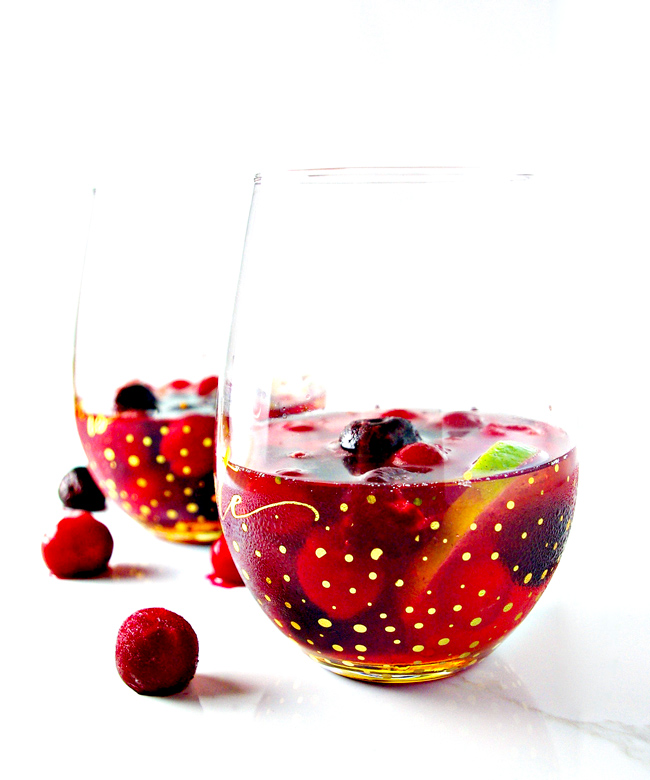 Take your party up a notch with this Cherry Lime Champagne Cocktail! A hint of rum with frozen cherries is just the ticket! | spiritedandthensome.com
