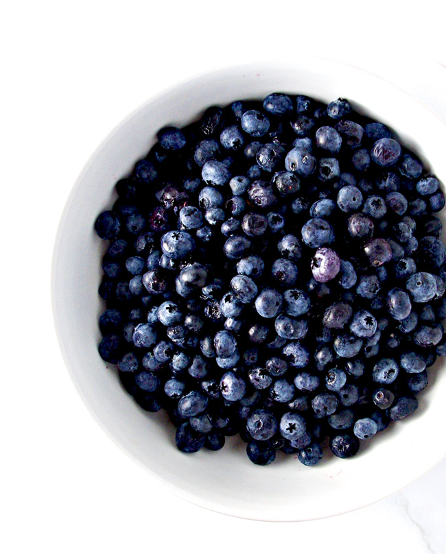 Blueberries in a white bowl for Grain-Free Blueberry Crumble! | spiritedandthensome.com