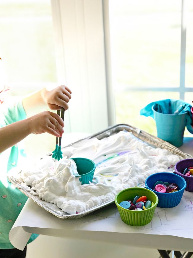 Twinkle making a shaving cream cupcake on her Rainbow Sensory Tray! | spiritedandthensome.com