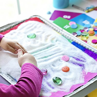 Twinkle palying with salt and gems on one of our Rainbow Sensory Trays! | spiritedandthensome.com