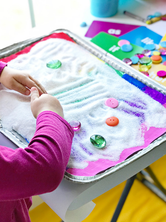 Twinkle plays with salt and gems on one of our Rainbow Sensory Trays! | spiritedandthensome.com