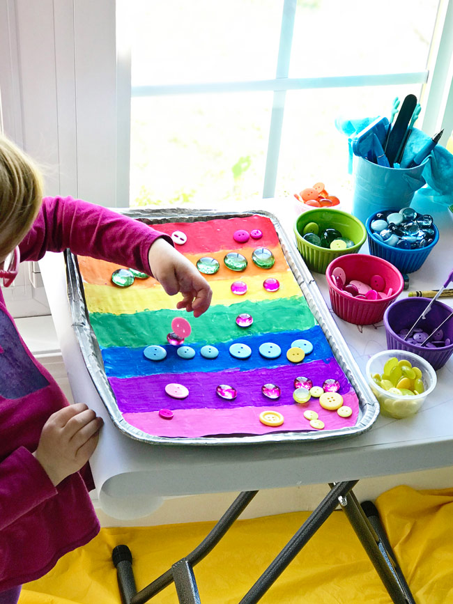 Twinkle plays with buttons and beads on one of our Rainbow Sensory Trays! | spiritedandthensome.com