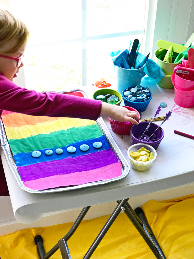 Twinkle plays with beads and buttons on her Rainbow Sensory Tray! | spiritedandthensome.com