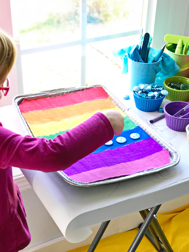 Twinkle plays with buttons on her Rainbow Sensory Tray! | spiritedandthensome.com
