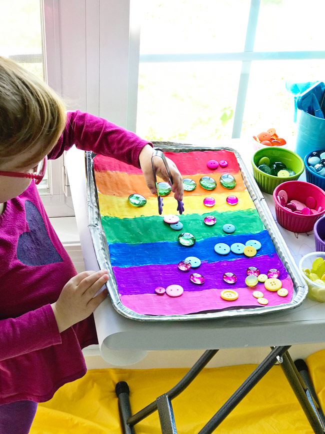 Twinkle using tongs with her Rainbow Sensory Tray! | spiritedandthensome.com