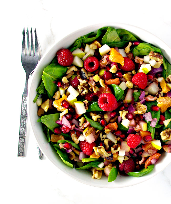 Pomegranate Pear Salad is full of citrus and berry flavors, along with savory onions, crunchy walnuts, and succulent leafy greens! Paleo, gluten-free, and dairy-free! | spiritedandthensome.com