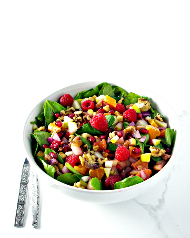 Pomegranate Pear Salad is full of citrus and berry flavors, succulent leafy greens, onions, and crunchy walnuts! | spiritedandthensome.com