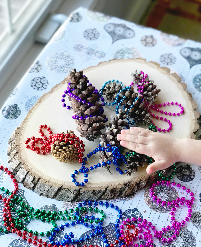 Tree cookies, bead necklaces, and pinecones are the perfect Christmas and holiday sensory play activities! | spiritedandthensome.com
