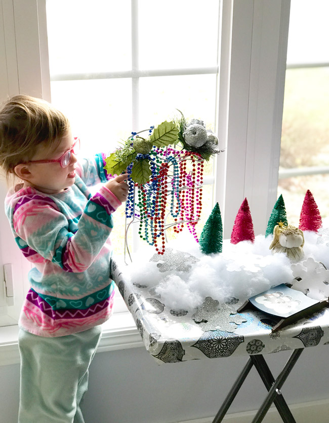 Twinkle playing with a makdeshift loose parts play Christmas tree! | spiritedandthensome.com
