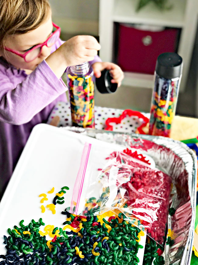 Pour dyed pasta into plastic containers for sensory play! How to dye pasta for sensory play recipe {gluten-free} | spiritedandthensome.com