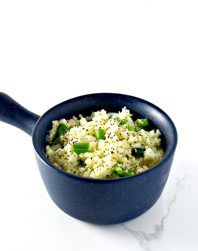 Cauliflower rice with green onions in a blue bowl. | spiritedandthensome.com