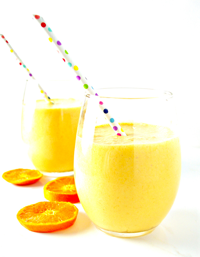 Two Dairy-Free Mandarin Orange Creamsicle Smoothies with mandarin oranges on a white background! | spiritedandthensome.com