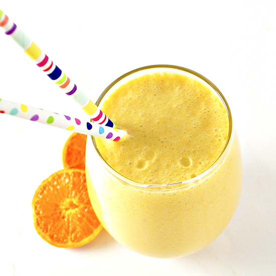 Dairy-Free Mandarin Orange Creamsicle Smoothie in a clear glass on a white background.