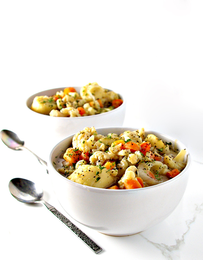 Soup in a white bowl on a white surface with silverware.   spiritedandthensome.com