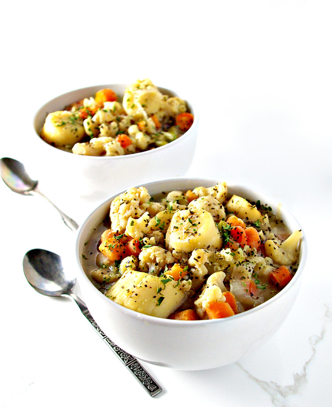 Dairy-free soup in a white porcelain bowl with silverware on a white marble surface.   spiritedandthensome.com