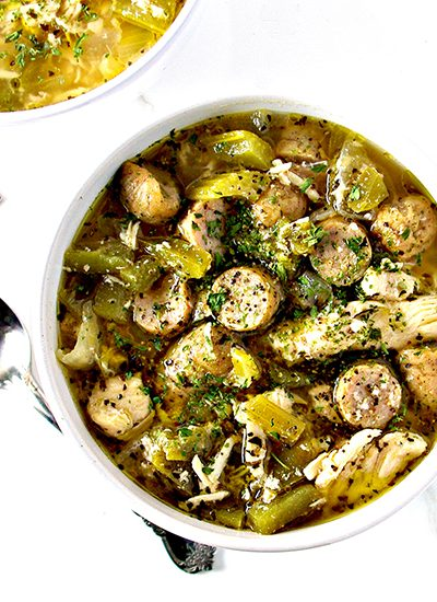 Sausage and chicken in a broth in a white bowl with silverware on a white marble surface. | spiritedandthensome.com