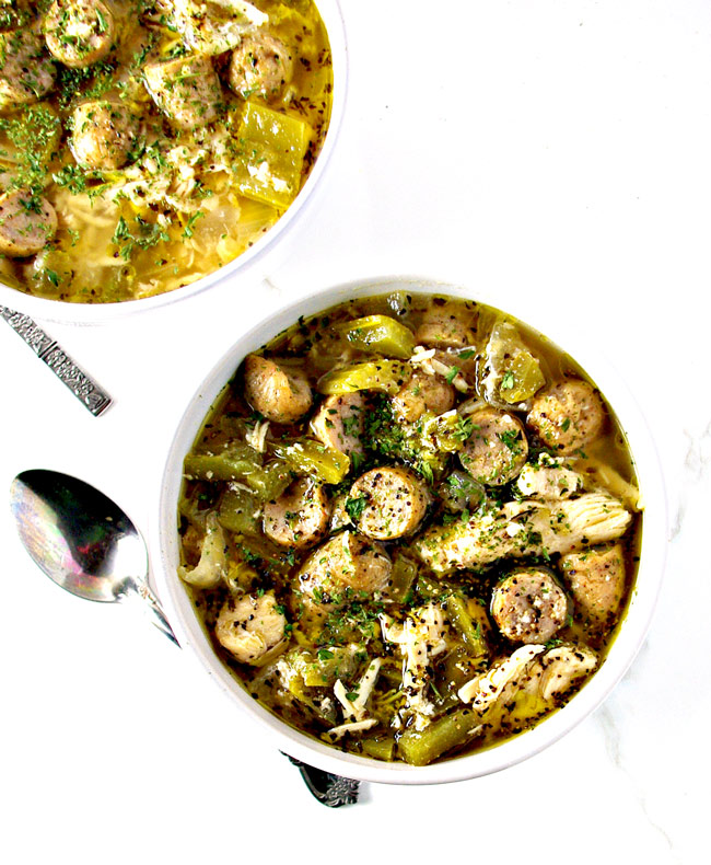 White chicken and sausage in a homemade broth in a porcelain bowl on a white marble surface.   spiritedandthensome.com
