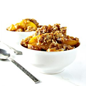 Gluten-Free Peach Crisp in two porcelain white dishes on a white marble surface with silverware.   spiritedandthensome.com