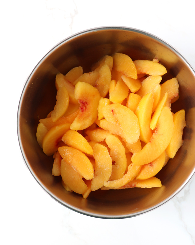 Frozen peaches thawing in a stainless steel bowl on a white marble surface.