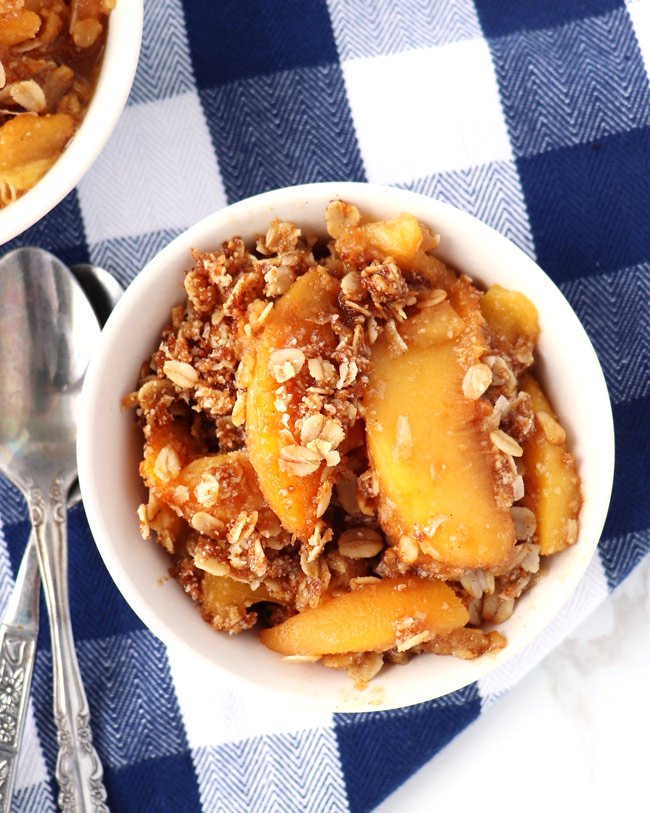 Gluten-Free Peach Crisp topped with gluten-free oatmeal and shredded coconut in a small white dish on a blue and white checked napkin.