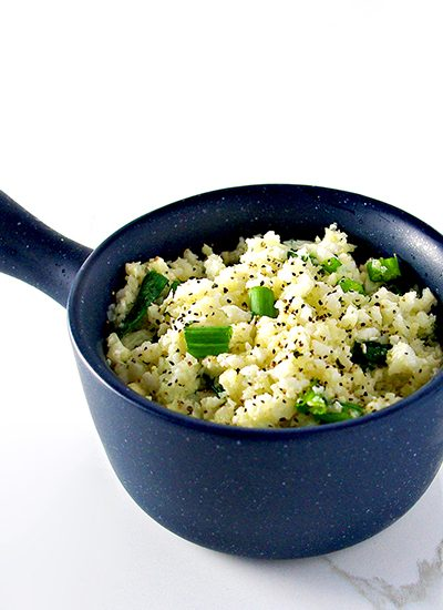 Cauliflower rice in a blue bowl with green onions and pepper. | spiritedandthensome.com