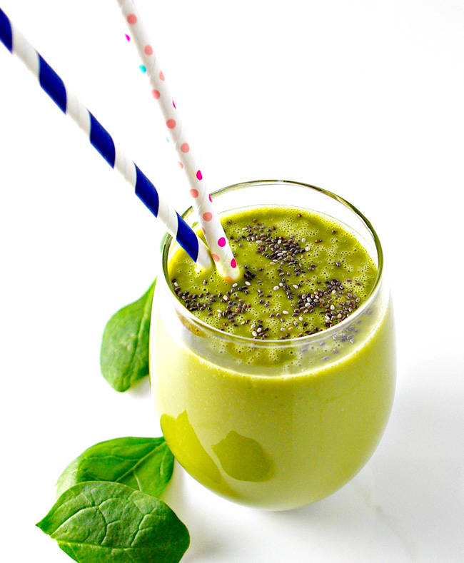 Matcha and chia seeds in a glass with straws, surrounded by fresh spinach leaves. | spiritedandthensome.com