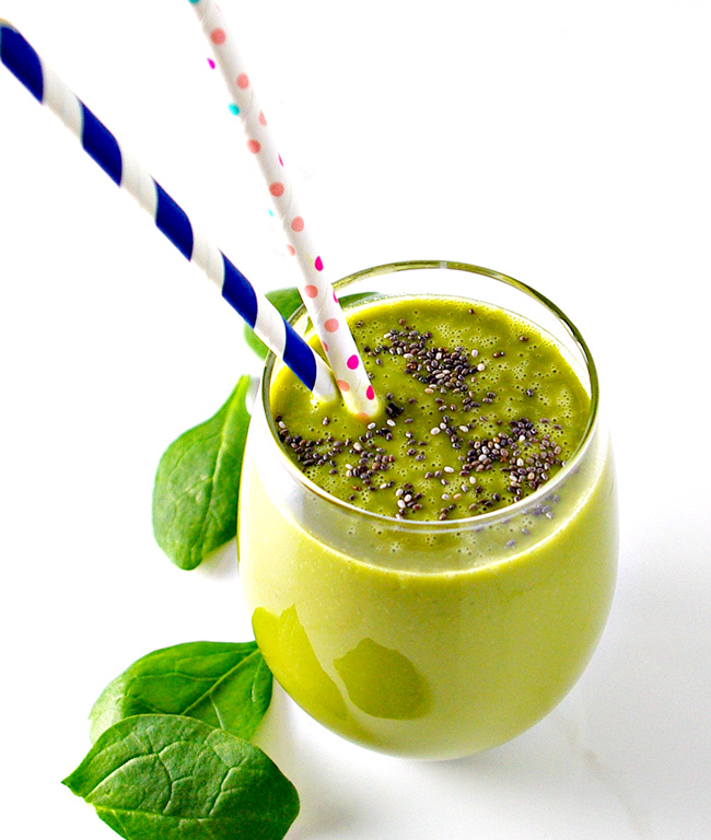 Matcha Mango Smoothie in a glass with a straw and spinach leaves. | spiritedandthensome.com