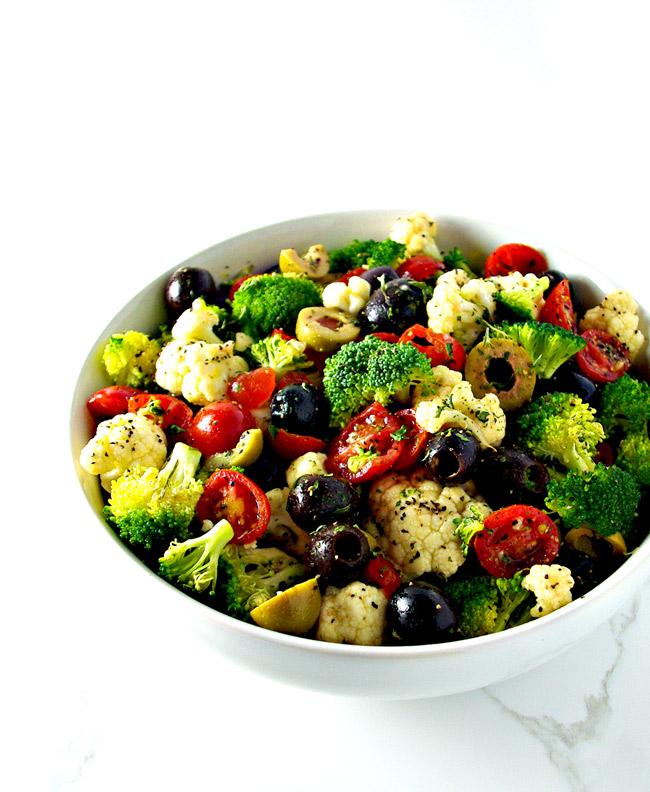 Broccoli Cauliflower Greek Salad in a white bowl on a marble surface | spiritedandthensome.com