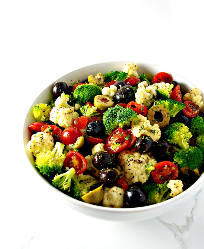 Broccoli, cauliflower, tomatoes, and olives in a white bowl! | spiritedandthensome.com