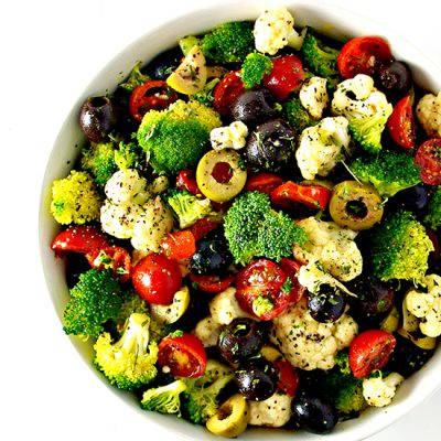 Broccoli, cauliflower, tomatoes, and olives in a white bowl on a white surface. | spiritedandthensome.com