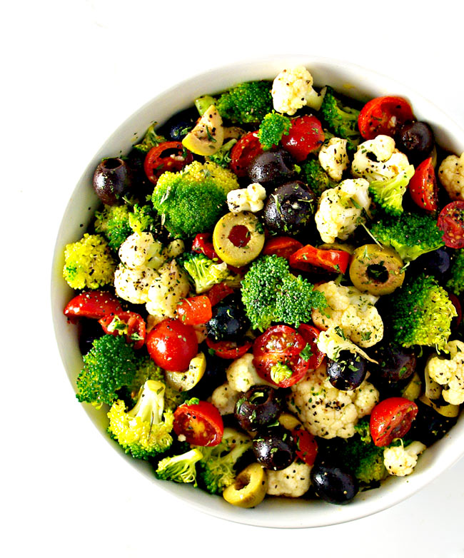 Broccoli, cauliflower, olives, and tomatoes in a white bowl. | spiritedandthensome.com