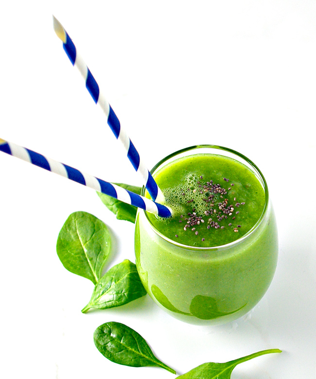 Green juice in a glass on a white marble surface.   spiritedandthensome.com