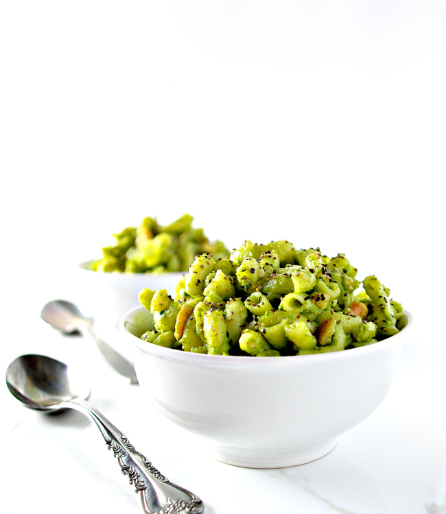 Basil pesto with gluten-free pasta in white dishes with silverware. | spiritedandthensome.com
