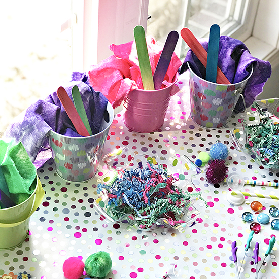 Easter grass, wood sticks, and pom poms with pails. | spiritedandthensome.com