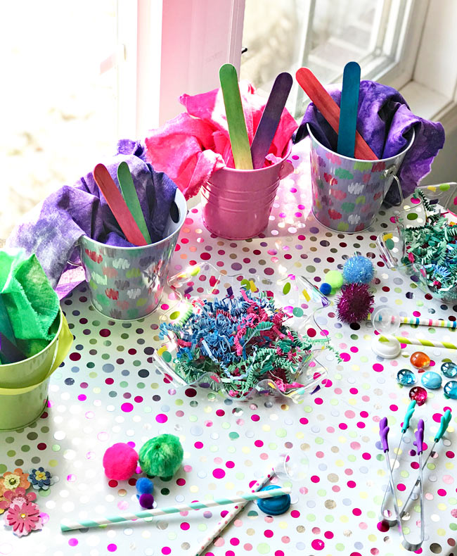 Small pails filled with wood sticks along with pom poms, gems, and Easter grass. | spiritedandthensome.com