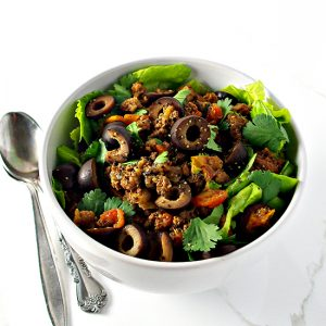 Ground beef in a white bowl with lettuce.   spiritedandthensome.com