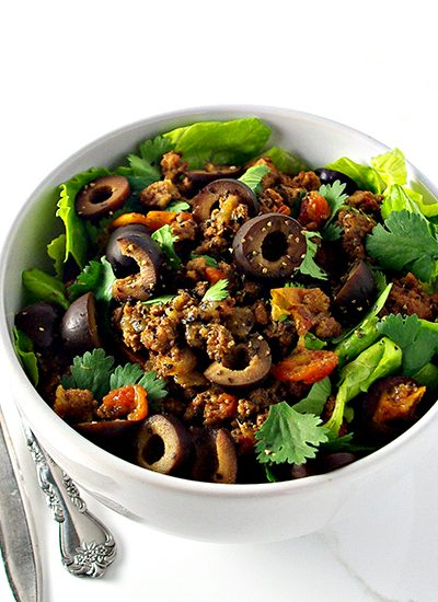 Ground beef in a white bowl with lettuce. | spiritedandthensome.com