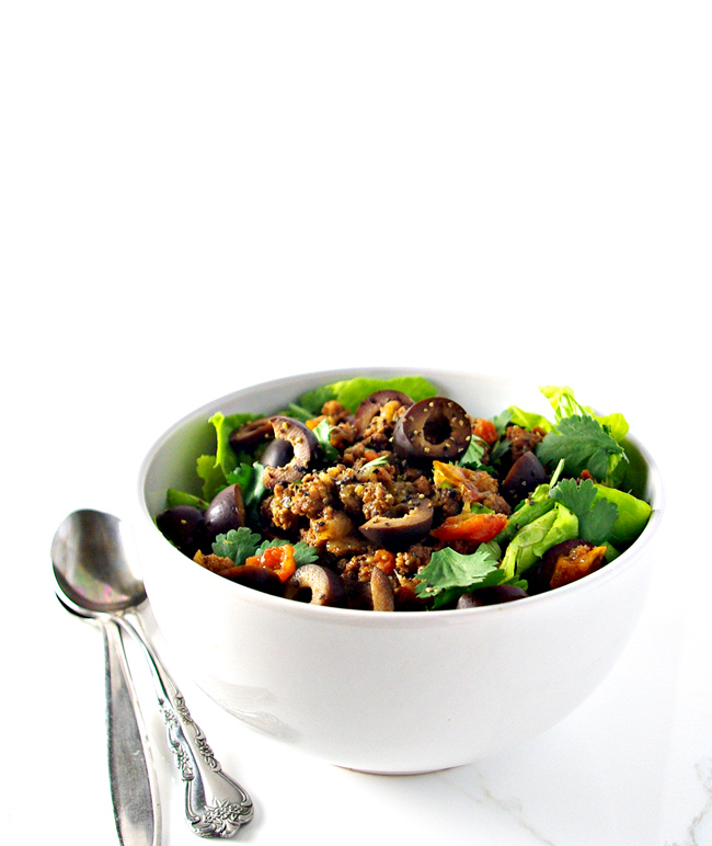 Ground beef with black olives, tomatoes, and lettuce in a white bowl on a marble surface. | spiritedandthensome.com