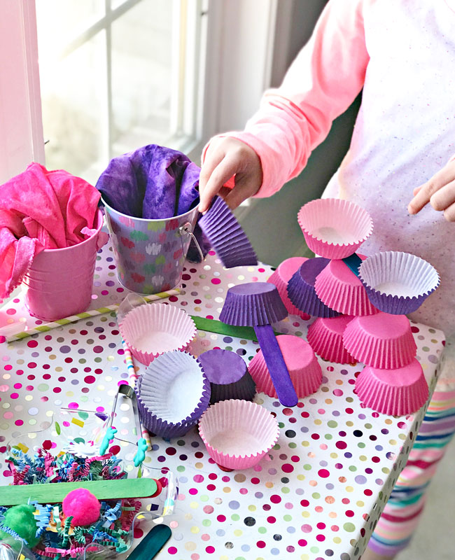Elementary student stacking muffin cups for loose parts play and STEM activities. | spiritedandthensome.com