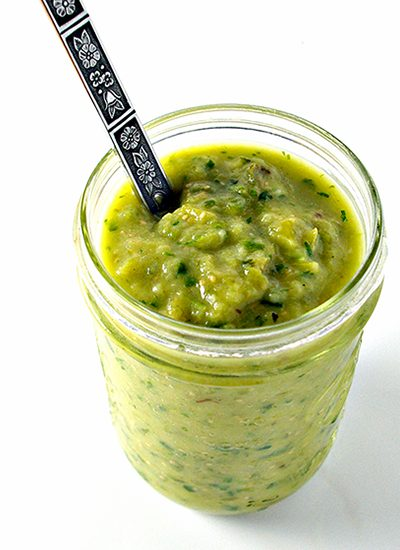 Roasted Salsa Verde in a glass jar with a spoon. | spiritedandthensome.com