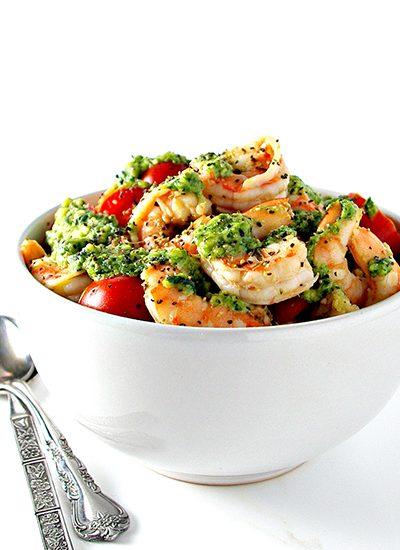 Shrimp, tomatoes, and pesto in a white bowl. | spiritedandthensome.com