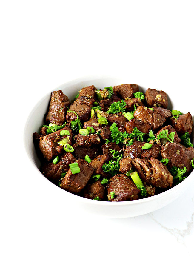 Gluten-free Garlic Butter Steak Bites are also dairy-free and paleo-friendly, flash-cooked to perfection, tossed in a garlic butter glaze, and topped with green onions and parsley! | spiritedandthensome.com