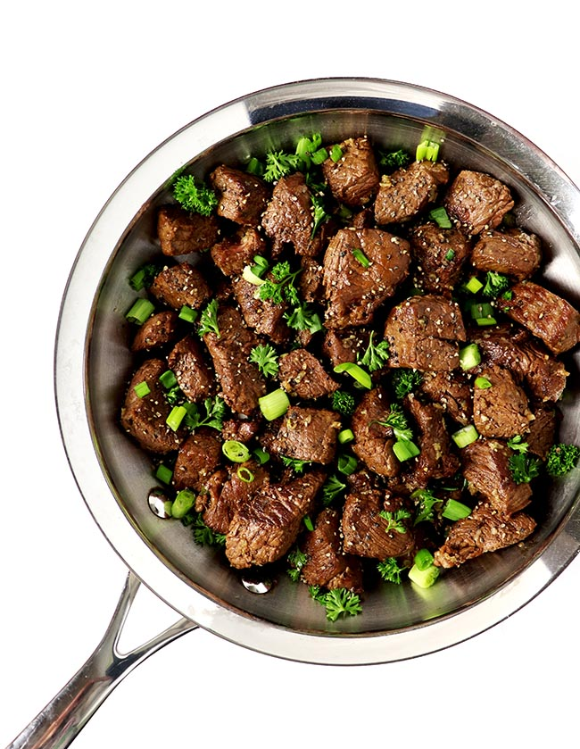 Garlic Butter Steak Bites can be prepared paleo-friendly with a garlic/coconut oil drizzle, and topped with green onions and fresh parsley! An easy appetizer recipe that also doubles as a main dish! | spiritedandthensome.com